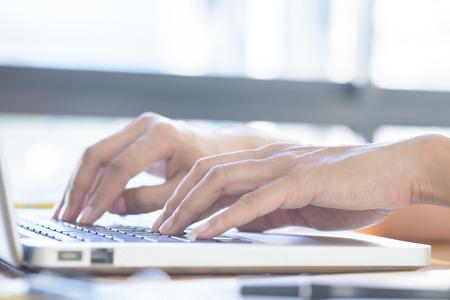 Asian woman using laptop to online shopping, working, typing.(selective focus) Standard-Bild