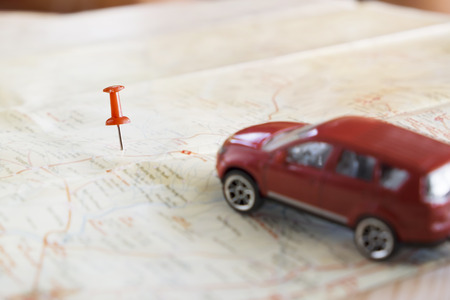 Travel concept background.Red pushpinpush point of location destination on map with blured red car