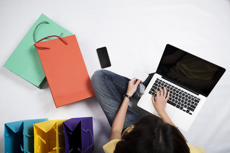 Top view of asian woman using laptop with black blank screen and colorful shopping bags, shoes on white floor. Online shopping concept. Top view concept.