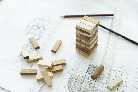 construction management: Planning, risk and strategy of project management in business, businessman and engineer gambling placing wooden block on a tower.Business and construction concept.