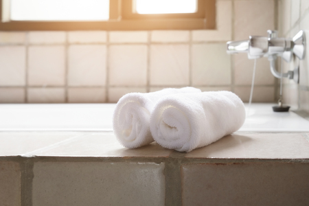 White row of towels beside the bathtub in the bathroom with morning sunlight.