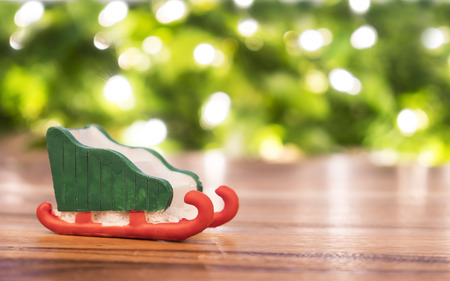 Toy santa sleigh on wooden floor and blur green and light bokeh Фото со стока