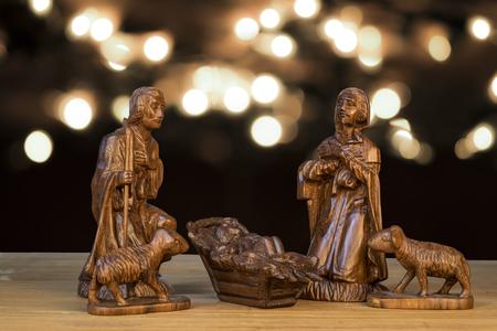Christmas scene with figurines. Baby Jesus, Mary, Joseph on light bokeh background.