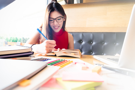 Collegian woman reading book in library. Education idea concept. Reading and researching for exam. The student life. Stock Photo