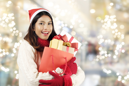 Christmas shopping concept. Woman holding a lot of gift boxes shopping mall background. Christmas, New year, Holidays, Celebration and people with happy time.