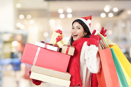 Happy girl shopping christmas gifts in shopping mall. Christmas and winter idea copyspace concept. Фото со стока