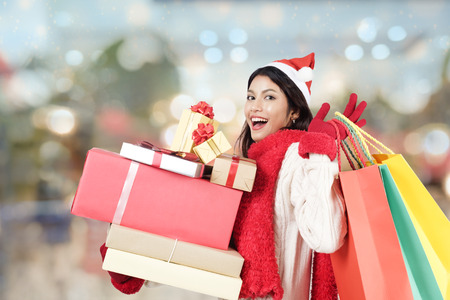 shoppingbag: Happy girl shopping christmas gifts in shopping mall. Christmas and winter idea copyspace concept. Stock Photo