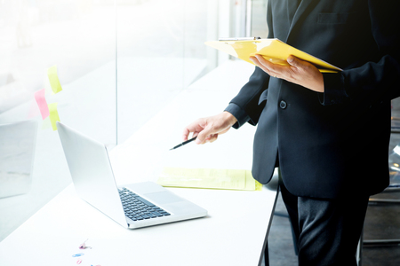 headman: Business man working at office with laptop and documents on his desk, consultant, analize business situation. Senior official checking work. Business office situation. Select focus at hand holding yellow file.