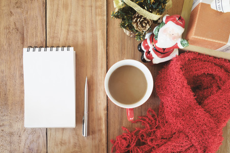 blank note: Top view of wooden table with blank white note paper , pen , cup of coffee , red scaft, gift box and christmas decorate.