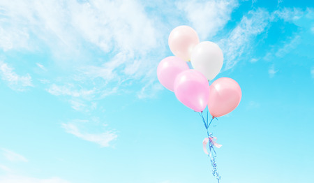 Colorful balloons flying on sky with a retro vintage filter effect. The concept of happy birthday in summer and wedding honeymoon party usage for background (vintage color tone)