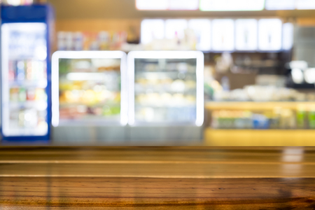cabinetry: Empty wooden table space platform and blurred bakery shop or coffee cafe background for product display montage. Stock Photo