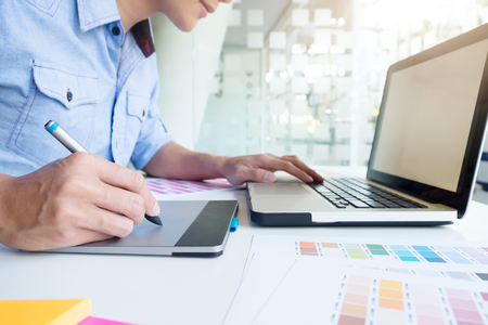 Freelance Photo editor, Artist, Graphic Designer working at desk in creative office. Artist drawing something on graphic tablet at the office. Stock Photo