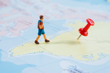 Mini figure traveler with red pushpin and a map travel concept.