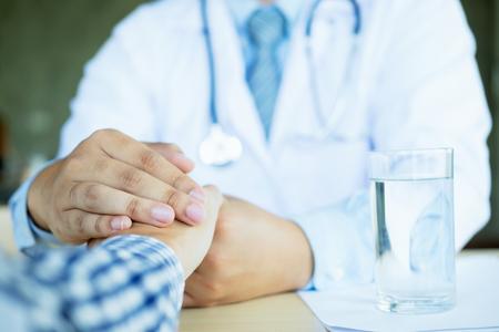 Hand of doctor reassuring his patient.
