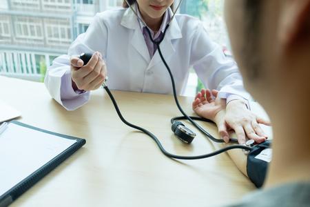 Docteur vérifier. Docteur vérifiant la pression artérielle du patient. Concept de soins de santé, hôpital et médecin