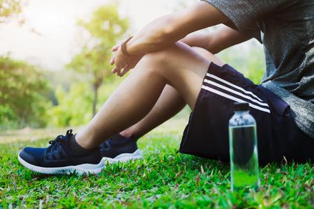 Atleet die op groen glas in park bij zonsondergang na het lopen met fles water (opzettelijke zonglans en uitstekende kleur) rusten.