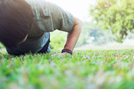Sport fitness man push-ups. Male athlete exercising push up outside in sunny sunshine. Fit male fitness model in crossfit exercise outdoors. Healthy lifestyle concept.
