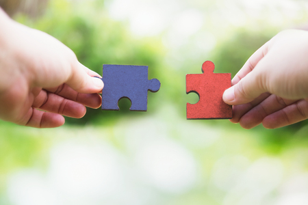 Businessman hand connecting jigsaw puzzle on green background. Business solutions, success and strategy concept.