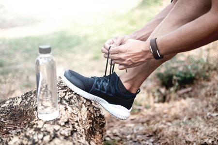 Runner tying shoelaces. Fitness and health care concept.
