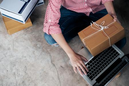 Junge Unternehmen starten den Online-Verkäufer, der einen Computer verwendet, um die Kundenaufträge von der E-Mail oder der Website aus zu überprüfen und Pakete für die Produkt-Büroausstattung vorzubereiten. Standard-Bild