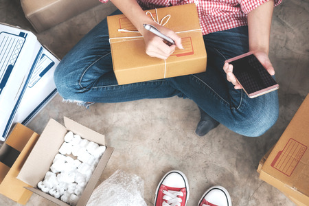 marketing online: Business Start up SME concept. Young startup entrepreneur small business owner working at home, packaging and delivery situation. Stock Photo