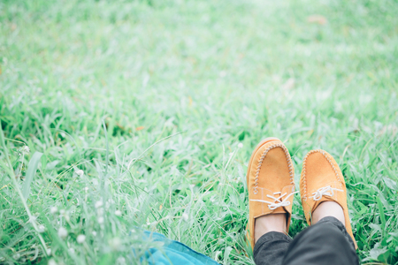 Woman feet who lay down and relax on green grass in the outdoor park. Relaxation and outdoor idea concept. Vintage tone color effect