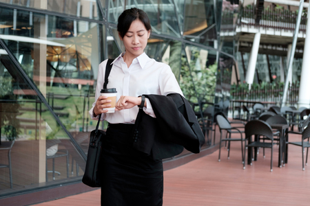 Business woman walking drinking coffee. Lawyer professional or similar walking outdoors happy holding disposable paper cup. Businesswoman smiling happy outside. Stock Photo