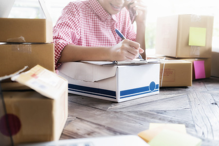 Business Start up SME concept. Young startup entrepreneur small business owner working at home, packaging and delivery situation. Stock Photo