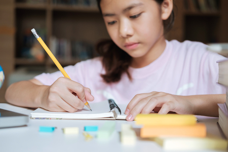 Education concept. Girl reading and writing and do homework in library of school. Seft study and learning.
