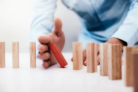 Zakenman stop van de hand domino's continu omvallen of risico met copyspace. Bedrijfsrisico, strategie en schaven concept idee. Stockfoto
