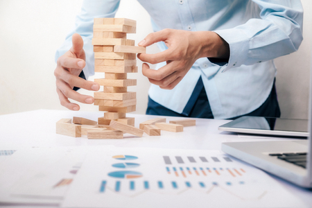 Businessman hand stop dominoes continuous toppled or risk with copyspace. Risk, Strategy, Planning management concept. Stock Photo - 89477983