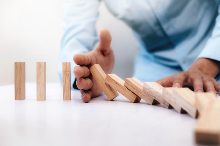 Businessman hand stop dominoes continuous toppled or risk with copyspace. Business risk, strategy and planing concept idea.