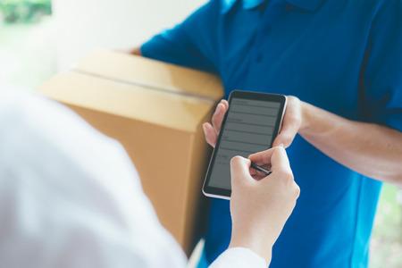 Anhängende Unterzeichnung der jungen Frau im digitalen Handy, nachdem zu Hause Paket vom Kurier empfangen worden ist.