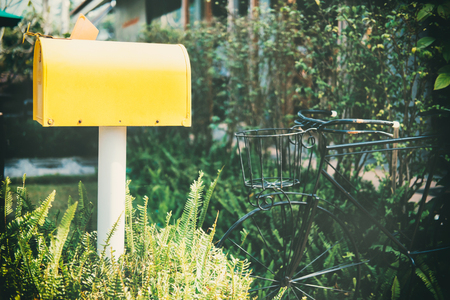 Old vintage yellow mail box in graden in front of the house. Stock Photo