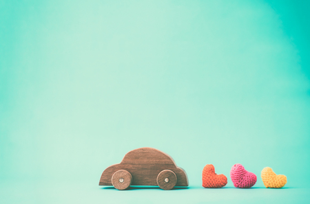 ooden car toy carrying red heart on top. Love , Valentine idea background concept.