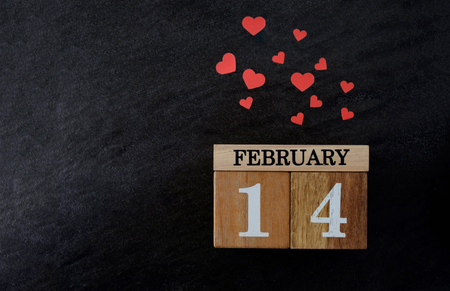 Wooden calendar show of February 14 with red heart on black texture background.