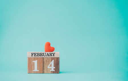 Wooden calendar show of 14th February  with red heart on pastel color background.