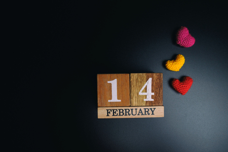 Wooden calendar show of February 14 with red heart on black texture background.  Stock Photo