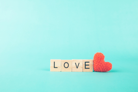 Love Valentine idea background concept. Love alphabet wood and red heart on paltel background.