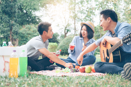 Young teen groups having fun picnic in park together. Relax and Leisure activity.