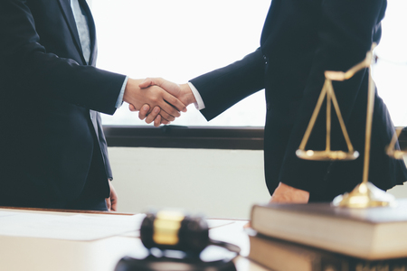 Law and Legal services concept. Lawyer and attorney having team meeting at law firm. Lawyer and businessman handshake. Stok Fotoğraf