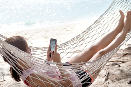 Woman using mobile phone on cozy mesh hammock at sea beach. Relaxation vacation and chilling on the sea beach.