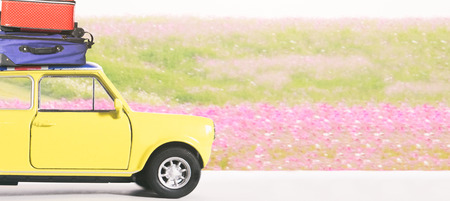Vintage yellow car on the spring flowers field with travel bags on the roof. Travel and Leisure trip in the summer and spring.