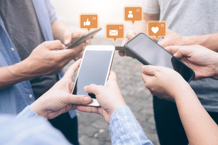 Group of young teen using mobile smartphone with icon social media and social network.  Stock Photo