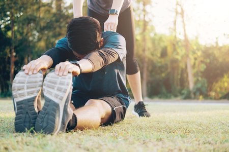 Young man and woman stretching in the park. Young couple warming up in morning.  Stock Photo