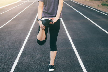 Woman runner stretching legs before run. Legs warming and stretching.