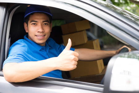 Delivery driver driving car with packages on seat outside the warehouse