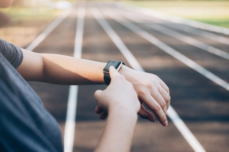 Young woman checking progress on smart watch. Female runner looking at smart watch heart rate monitor. Stock Photo
