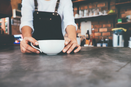 Cropped shot of barista in apron holding cup of coffee on counter in cafe. Start up small business owner food and drink concept.  Stock Photo