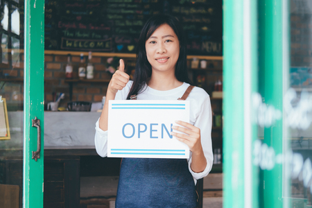 Open Small business: Happy owner of a cafe. Young startup owner small cafe shop
